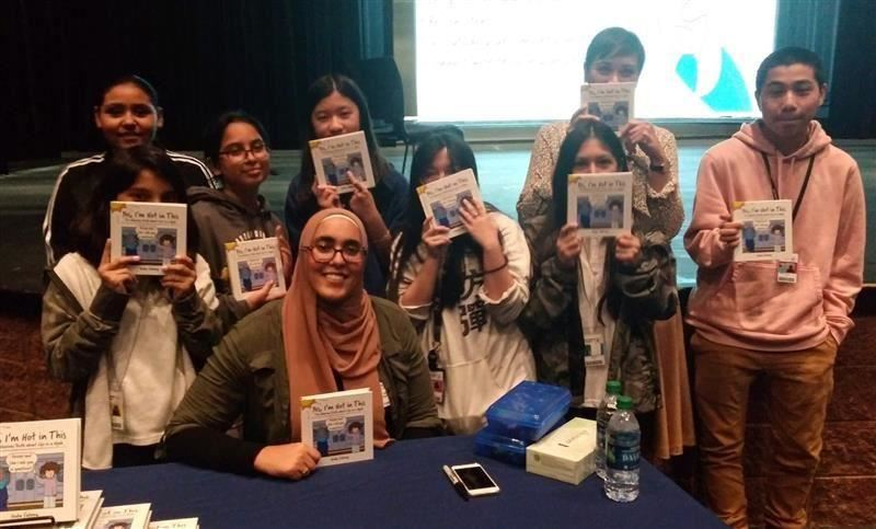 Huda Fahmy with students holding books