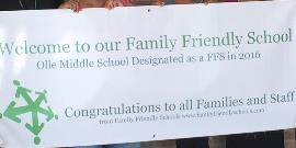 Picture of parents and staff members holding a banner - Olle Middle School a Family Friendly School