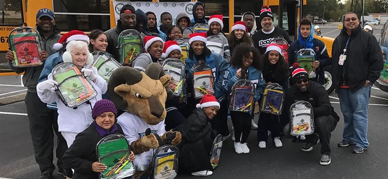 Photo of Stuff-A-Bus helpers holding backpacks