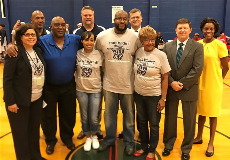 Photo of Dwight Mitchell's family with Alief ISD staff during the gym dedication ceremony