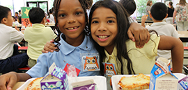 Photo of two female elementary students eating lunch