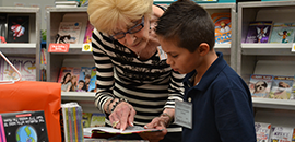 Photo of volunteer reading to a student